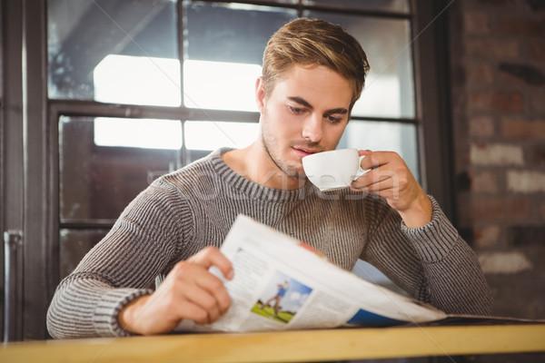 Handsome man drinking coffee and reading newspaper Stock photo © wavebreak_media