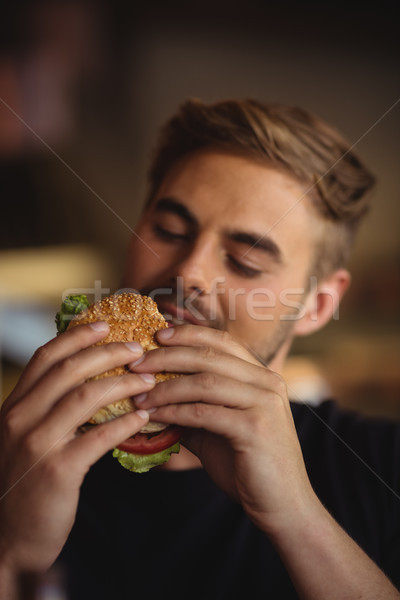 Primer plano hombre comer Burger restaurante hotel Foto stock © wavebreak_media
