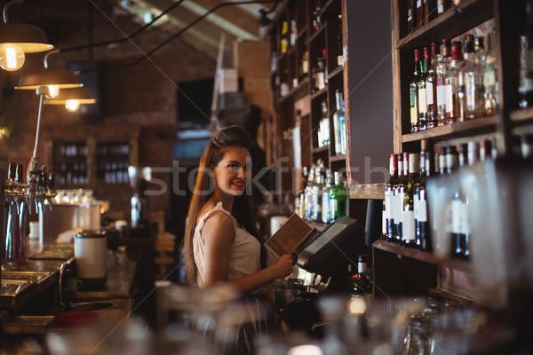 Female bar tender holding menu Stock photo © wavebreak_media