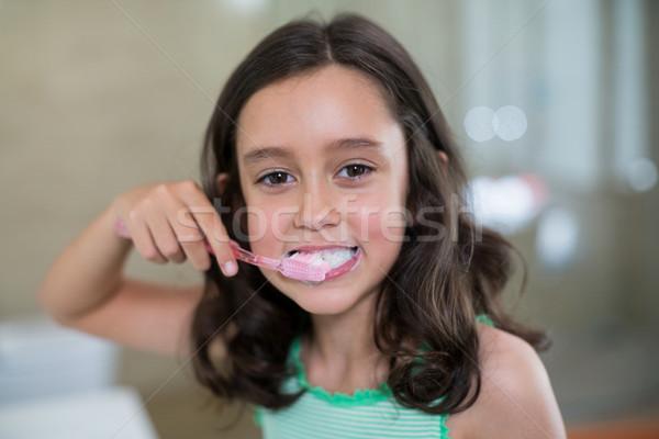 Portrait of smiling girl brushing her teeth in bathroom Stock photo © wavebreak_media