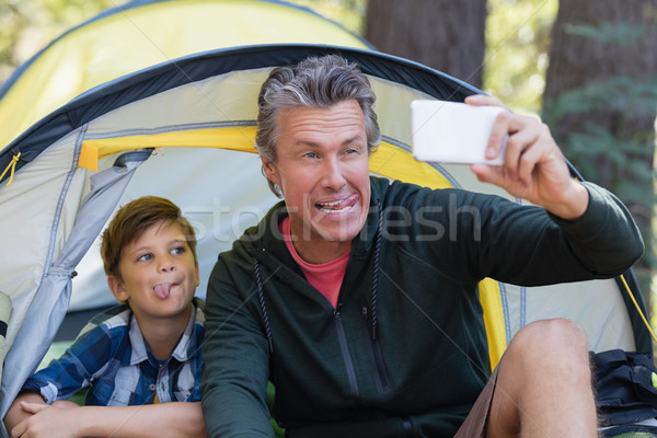 Playful father and son taking selfie in tent Stock photo © wavebreak_media