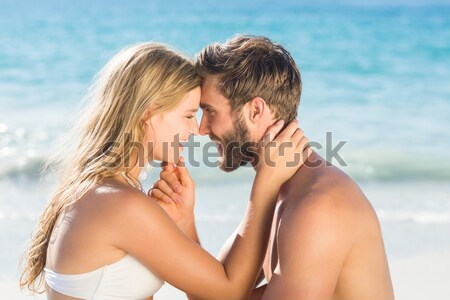 Side view of young couple sitting face to face at beach Stock photo © wavebreak_media