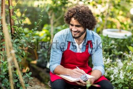Smiling man writing on notepad while resting on tree trunk Stock photo © wavebreak_media