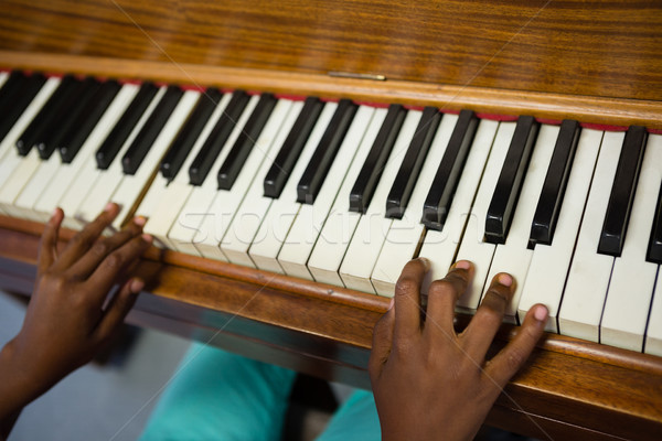 High angle view of boy playing piano while sitting in classroom Stock photo © wavebreak_media