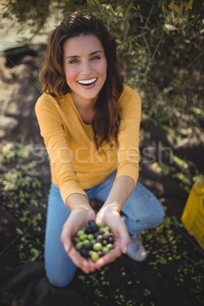 Glimlachende vrouw tonen olijven hurken veld boerderij Stockfoto © wavebreak_media