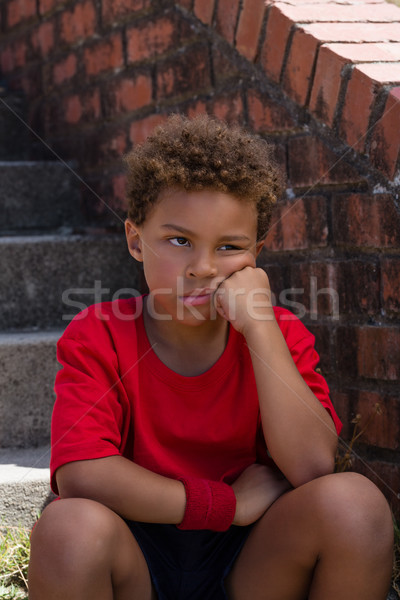 Upset boy sitting on staircase in the boot camp Stock photo © wavebreak_media