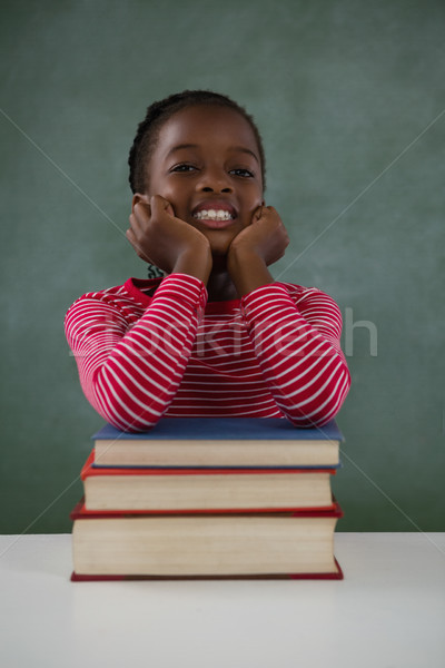 Schoolgirl leaning on books stack against chalkboard in classroom Stock photo © wavebreak_media