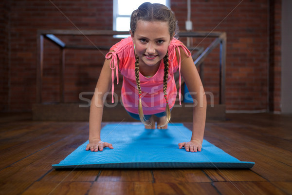 Portrait of happy teenage girl doing pushup Stock photo © wavebreak_media