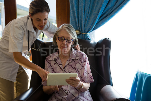 Female doctor assisting woman in using tablet at retirement home Stock photo © wavebreak_media