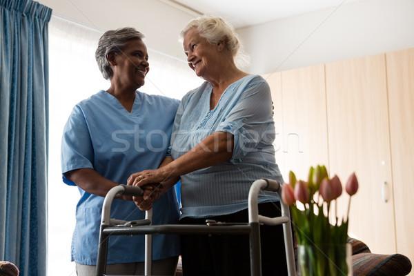 Nurse assisting senior patient in walking with walker Stock photo © wavebreak_media