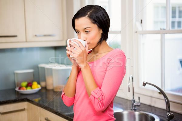 Standing brunette drinking by cup Stock photo © wavebreak_media