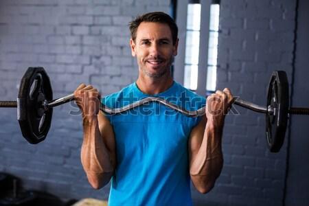 Muscular man lifting barbell on bench Stock photo © wavebreak_media