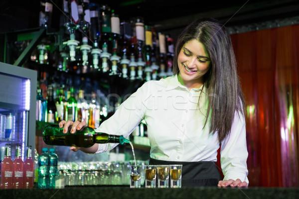 Pretty bartender pouring tequila into glasses Stock photo © wavebreak_media