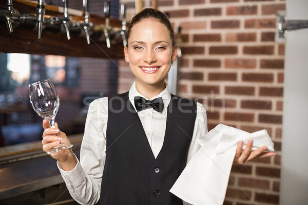 Barmaid holding a wine glass and towel Stock photo © wavebreak_media