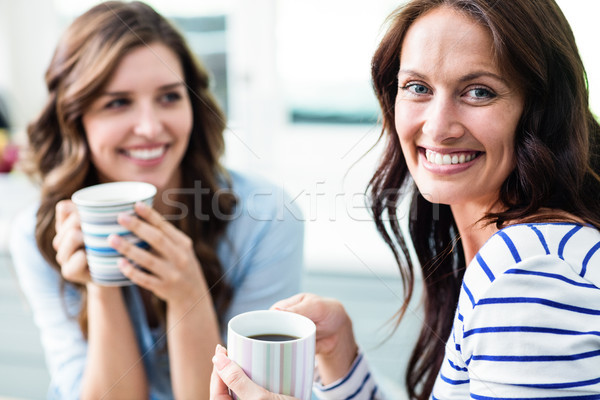 Cheerful female friends holding coffee mugs while sitting at tab Stock photo © wavebreak_media