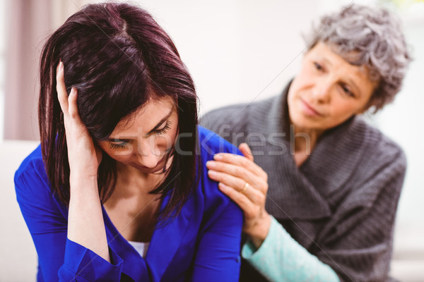 Mother comforting sad daughter sitting on sofa Stock photo © wavebreak_media