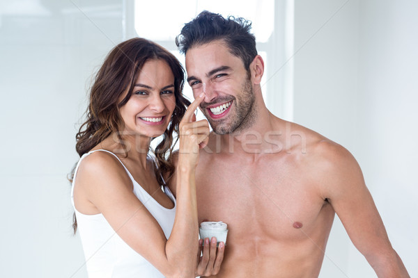 Stock photo: Wife applying cream on husband face at home