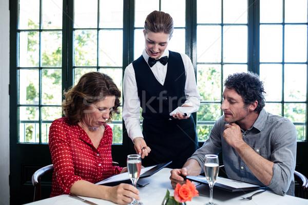 Waitress assisting a couple while selecting menu Stock photo © wavebreak_media