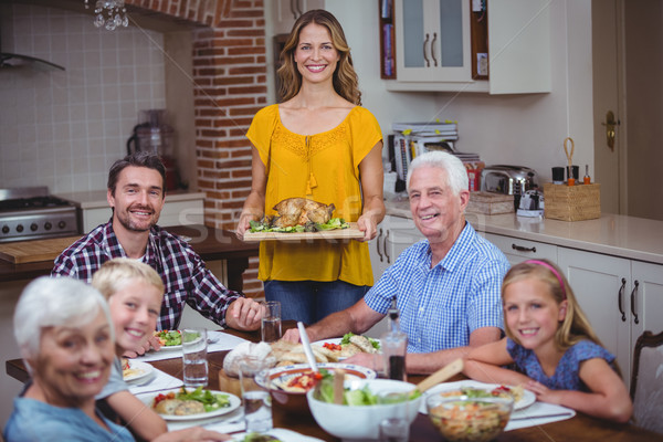 Smiling family at dining table with mother standing Stock photo © wavebreak_media