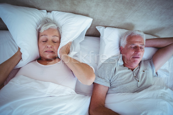 Senior woman blocking ears with pillow while husband snoring on  Stock photo © wavebreak_media