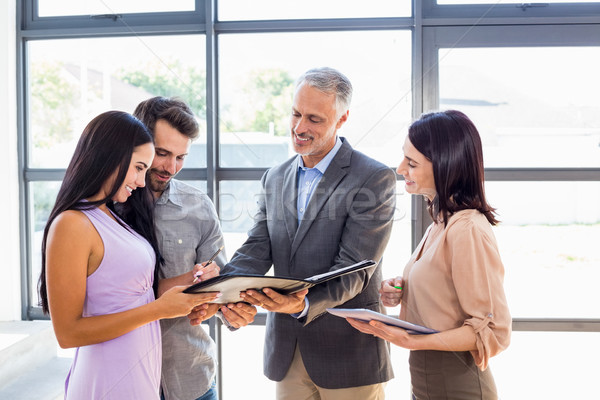 Real estate agent handing over agreement paper to couple Stock photo © wavebreak_media