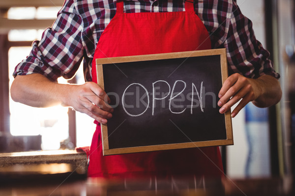 Mid section of waiter showing chalkboard with open sign Stock photo © wavebreak_media