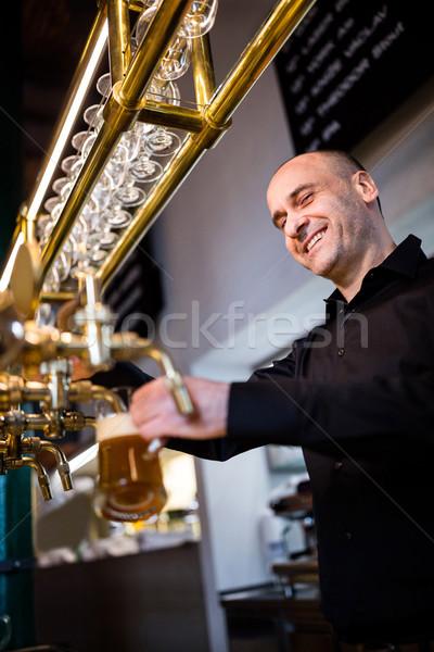 Brewer filling beer in beer glass from beer pump Stock photo © wavebreak_media