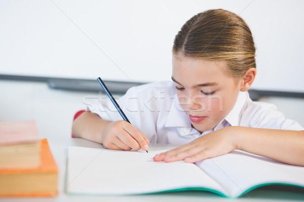 Schoolkid doing homework in classroom Stock photo © wavebreak_media