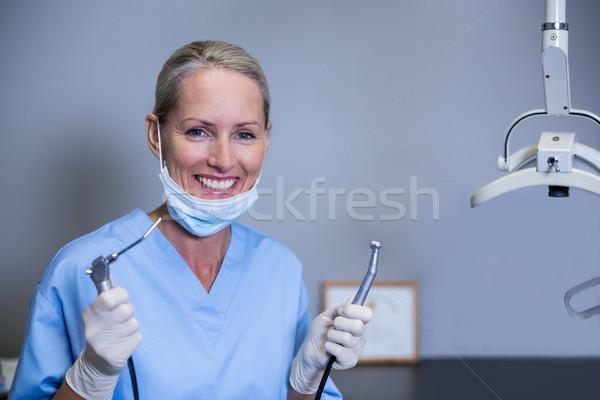 Smiling dental assistant holding dental tools in clinic Stock photo © wavebreak_media