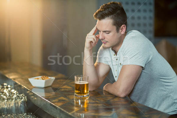 Thoughtful man with glass of whisky sitting at bar counter Stock photo © wavebreak_media