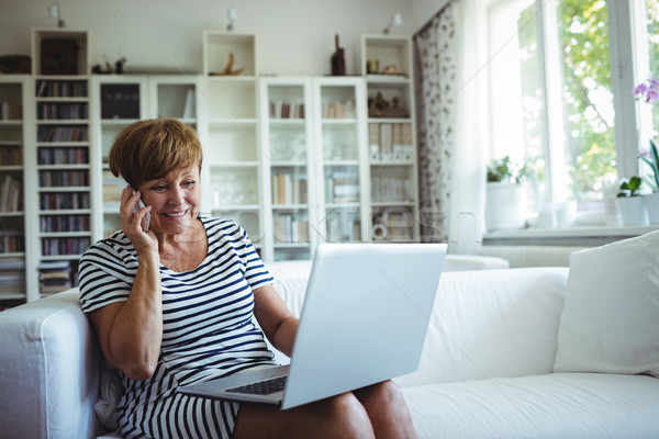 Senior woman talking on mobile phone while using laptop in living room Stock photo © wavebreak_media
