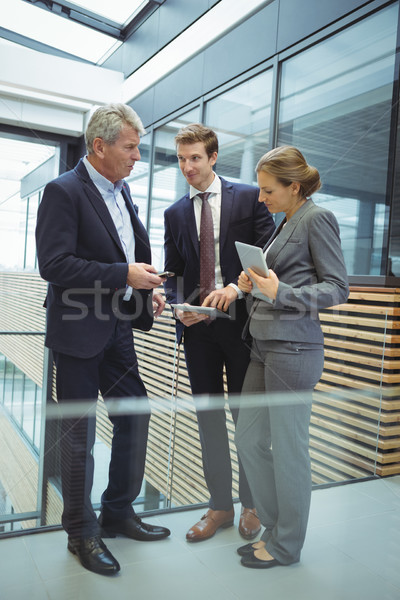Businesspeople discussing over electronic devices in the passageway Stock photo © wavebreak_media