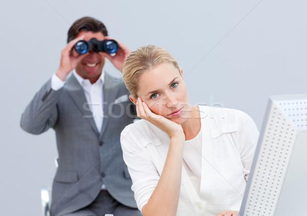 Stock photo: Blond businesswoman annoyed by a man looking through binoculars