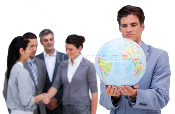 Handsome business man and his team looking at a terrestrial glob Stock photo © wavebreak_media