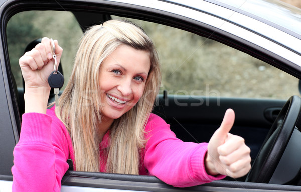 Jolly female driver showing a key after bying a new car  Stock photo © wavebreak_media