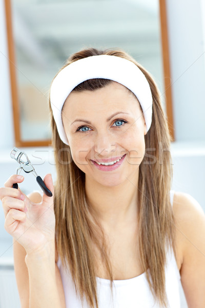 Smiling woman holding an eyelash curler looking at the camera in the bathroom at home Stock photo © wavebreak_media