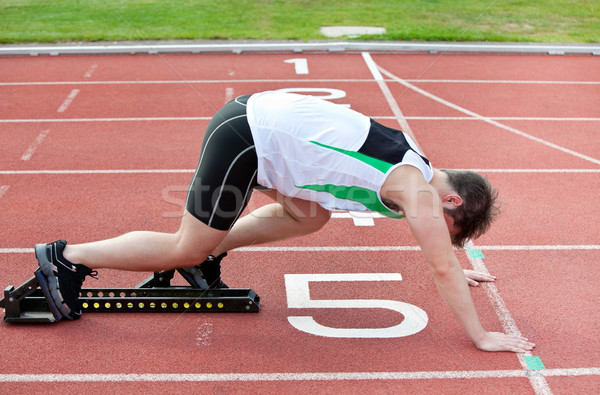 athletic man on the starting line putting his foot in the starting block  in a stadium  Stock photo © wavebreak_media