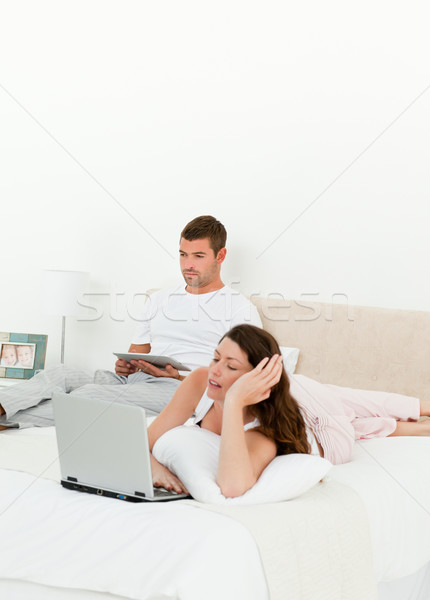 Pretty woman working on her laptop while her husband is reading a book in their bedroom Stock photo © wavebreak_media