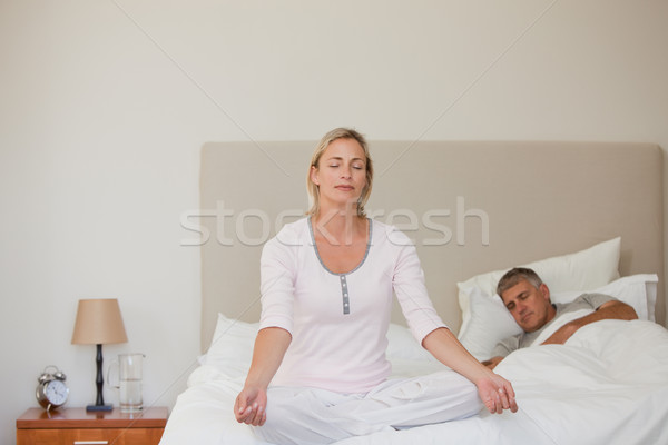Stock photo: Lovely woman practicing yoga on her bed