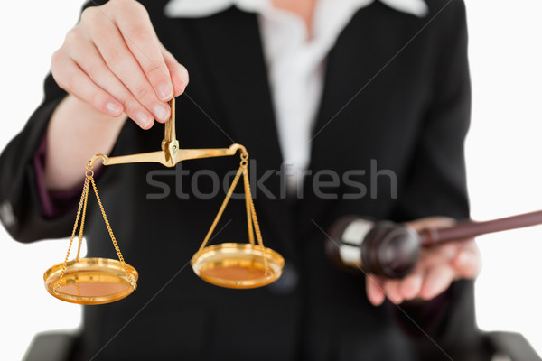 Young woman holding scales of justice and a gavel with the camera focus on the scales against a whit Stock photo © wavebreak_media