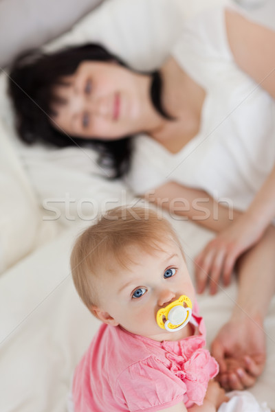 Stock photo: Cute baby looking at the camera while her mother is lying on a bed in her appartment