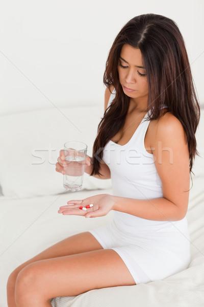 dark-haired woman having stomach ache taking pills in bedroom Stock photo © wavebreak_media