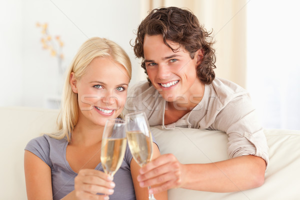 Lovely couple making a toast while looking at the camera Stock photo © wavebreak_media