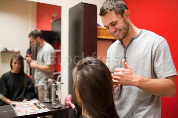 Smiling male hairdresser cutting hair with scissors Stock photo © wavebreak_media
