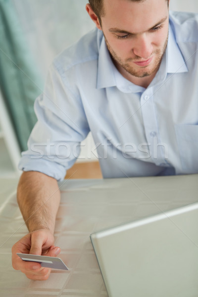 Stock photo: Young businessman with credit card on his laptop