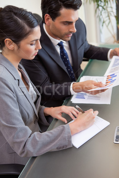 Portrait of sales persons studying statistics in a meeting room Stock photo © wavebreak_media