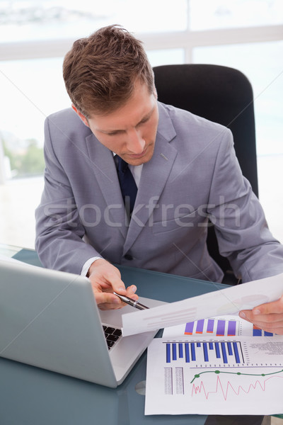 Empresario escritorio mirando estadística negocios papel Foto stock © wavebreak_media