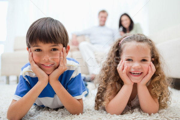 Happy smiling kids lying on the carpet with parents behind them Stock photo © wavebreak_media