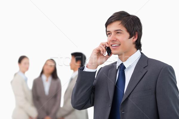 Venditore parlando telefono cellulare colleghi dietro bianco Foto d'archivio © wavebreak_media