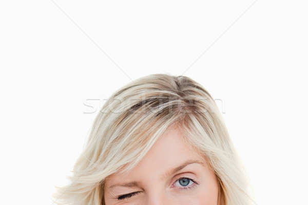 Upper part of the face of a woman blinking an eye againt a white background Stock photo © wavebreak_media